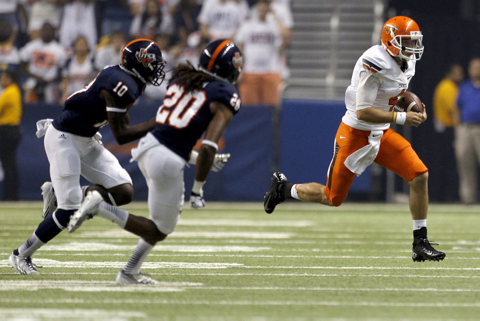 Photo - Oklahoma State's J.W. Walsh (4) gets by UTSA's Brian King (10) and Andre Brown (20)  during the first half of a college football game between the University of Texas at San Antonio Roadrunners (UTSA) and the Oklahoma State University Cowboys (OSU) at the Alamodome in San Antonio, Saturday, Sept. 7, 2013.  Photo by Sarah Phipps, The Oklahoman