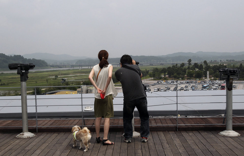 Photo - A couple uses binoculars to watch toward North Korea at the Imjingak Pavilion near the border village of Panmunjom which has separated the two Koreas since the Korean War, in Paju, South Korea, Saturday, June 7, 2014. North Korea has detained a 56-year old man from Ohio, accusing him of an unspecified crime after he traveled to the communist-led country as a tourist, the nation's state news agency and the man's family said Friday. (AP Photo/Ahn Young-joon)