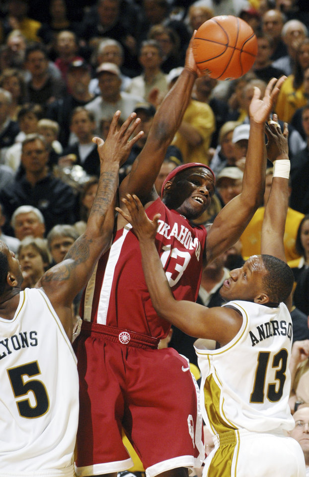 Photo - UNIVERSITY OF OKLAHOMA, OU: Oklahoma's Willie Warren, center, gets a pass off as Missouri's Leo Lyons, left, and Michael Anderson Jr., right, surround him during the first half of an NCAA college basketball game Wednesday, March 4, 2009, in Columbia, Mo. (AP Photo/L.G. Patterson) ORG XMIT: MOLG105