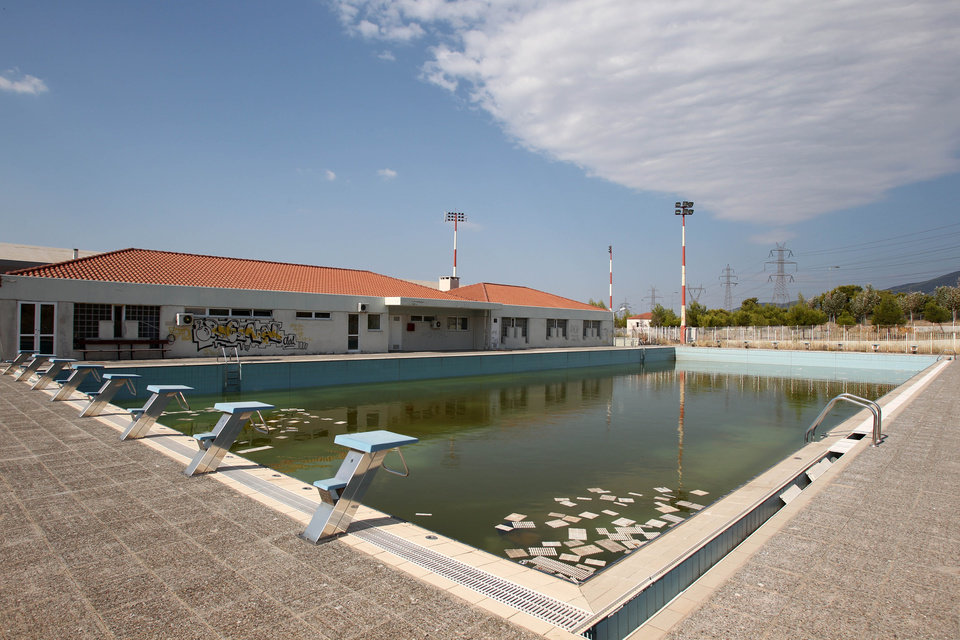 Photo - FILE - In this Thursday, Aug. 2, 2012, file photo, murky water and rubbish fill an abandoned training pool for athletes at the Olympic village on the northern fringes of Athens. The legacy of Athens' Olympics has stirred vigorous debate, and Greek authorities have been widely criticized for not having a post-Games plan for the infrastructure. While some of the venues built specifically for the games have been converted for other uses, many are underused or abandoned, and very few provide the state with any revenue. Some critics even say that the multibillion dollar cost of the games played a modest role in the nation's 2008 economic meltdown.(AP Photo/Thanassis Stavrakis, File)