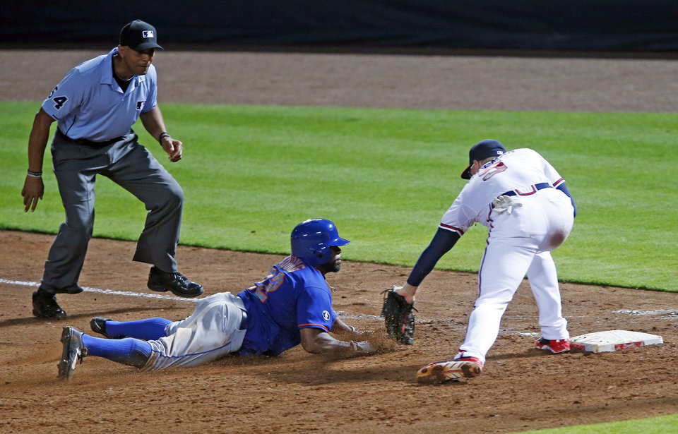 Photo - New York Mets' Eric Young Jr. (22) is tagged out by Atlanta Braves first baseman Freddie Freeman (5) while trying to get back to first base after being caught in a rundown in the fifth inning of a baseball game in Atlanta, Wednesday, July 2, 2014.  Atlanta won 3-1. (AP Photo/John Bazemore)