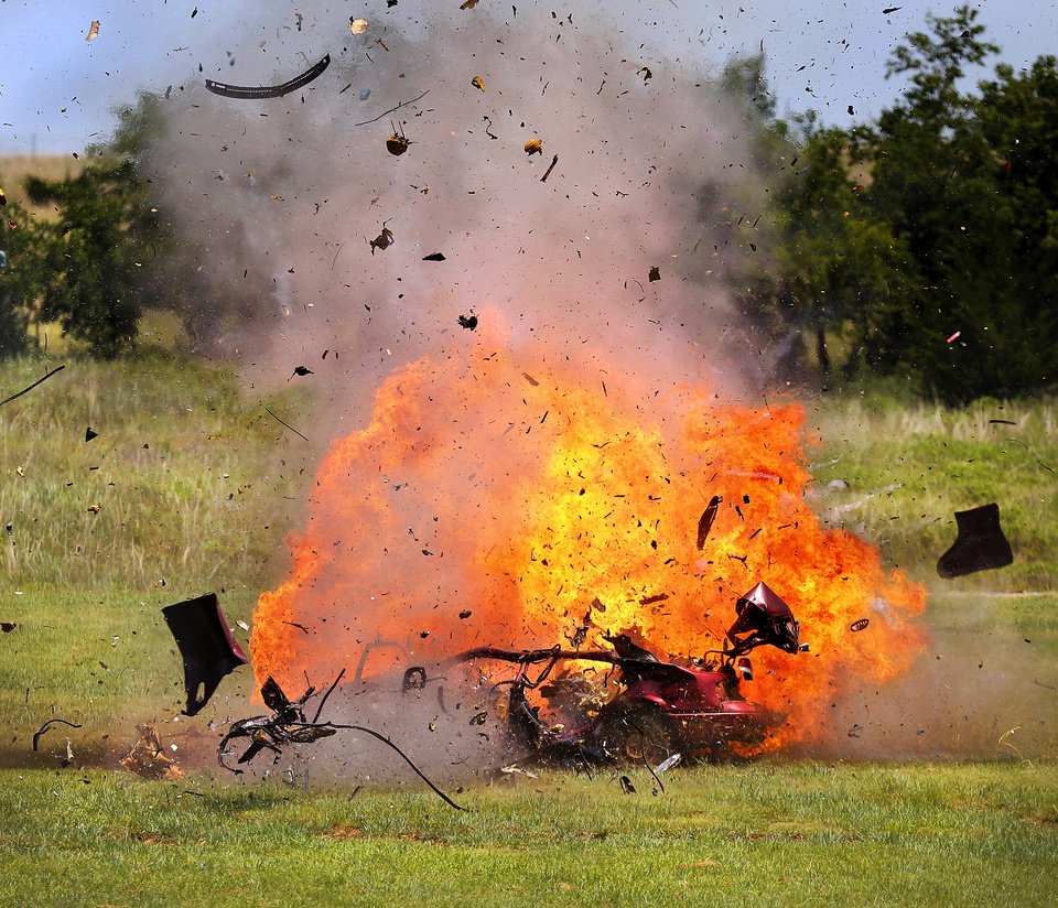 A  car is engulfed in a fireball less than one second after an explosive charge inside the vehicle was detonated by a police bomb squad team during a demonstration.  The OCPD bomb squad demonstrated some of its equipment for about 30 high school students  who are members of the current class of the department's Student Police Academy, which is hosted by the Police Athletic League. Bomb squad members showed off the unit's robot capabilities and detonated pre-set explosives inside a car so the students could witness the power of a bomb. The event was held Wednesday afternoon, July 9, 2014, at the OCPD  firearms range in southeast Oklahoma City.  Photo by Jim Beckel, The Oklahoman