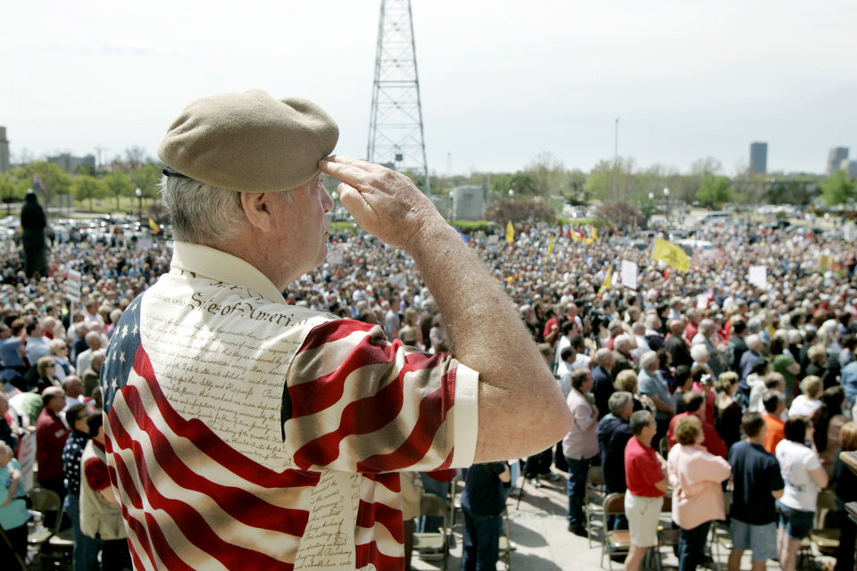 Photo - Dan Ward salutes during the Pledge of Allegiance during a Tax Day protest on the south steps of the State Capitol in Oklahoma City, Oklahoma April 15, 2009.  Photo by Steve Gooch, The Oklahoman