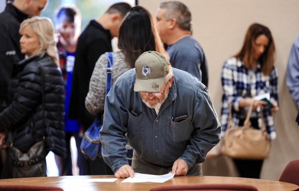 Photo - John Marx reads over the sample ballot before casting his vote on election day at the International Pentecostal Assembly in Yukon, Okla. on Tuesday, Nov. 6, 2018. Photo by Chris Landsberger, The Oklahoman