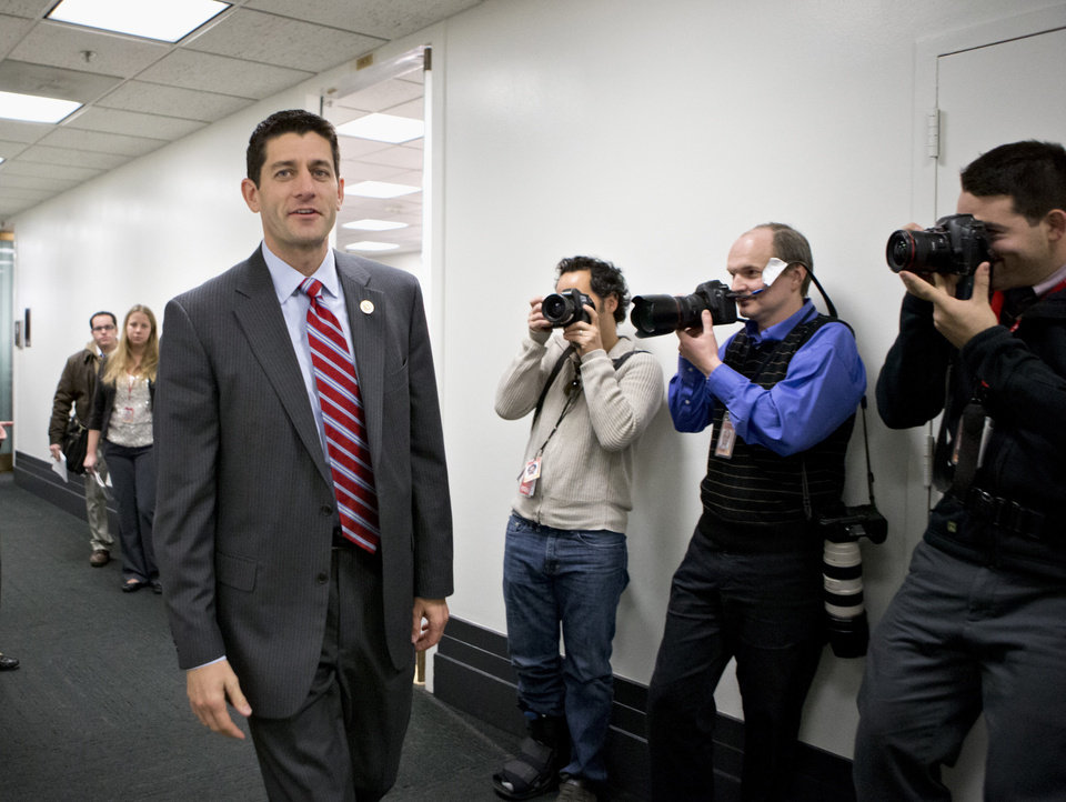 Photo - FILE - This Nov. 28, 2012 file photo shows House Budget Committee Chairman Rep. Paul Ryan, R-Wis. walking on Capitol Hill in Washington.  House Republicans say they may seek a short-term extension of the government's debt limit in the next few weeks, a move that would avoid an immediate default by the Treasury. Ryan provided no details on the duration of any extension or conditions that might be attached as he appeared at a news conference during a break at a three-day retreat of the rank and file in historic Williamsburg, Va.  (AP Photo/J. Scott Applewhite, File)
