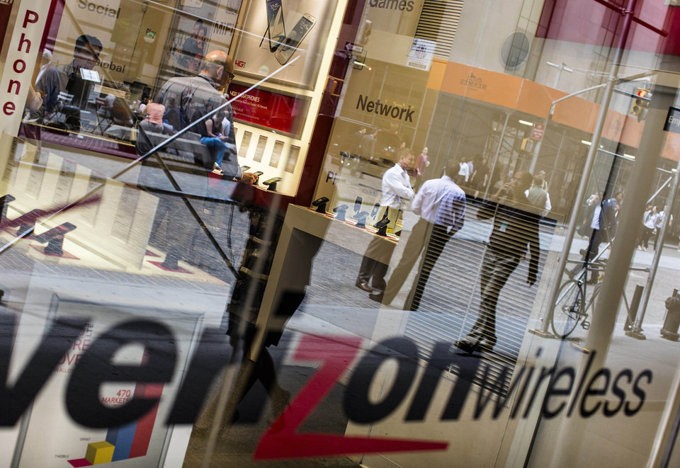 Photo - Pedestrians are reflected in the store window of a Verizon Wireless store near the New York Stock Exchange in lower Manhattan, Thursday, June 6, 2013, in New York. The National Security Agency is currently collecting the telephone records of millions of U.S. customers of Verizon under a top secret court order, said Britain's guardian newspaper said Wednesday. (AP Photo/John Minchillo)