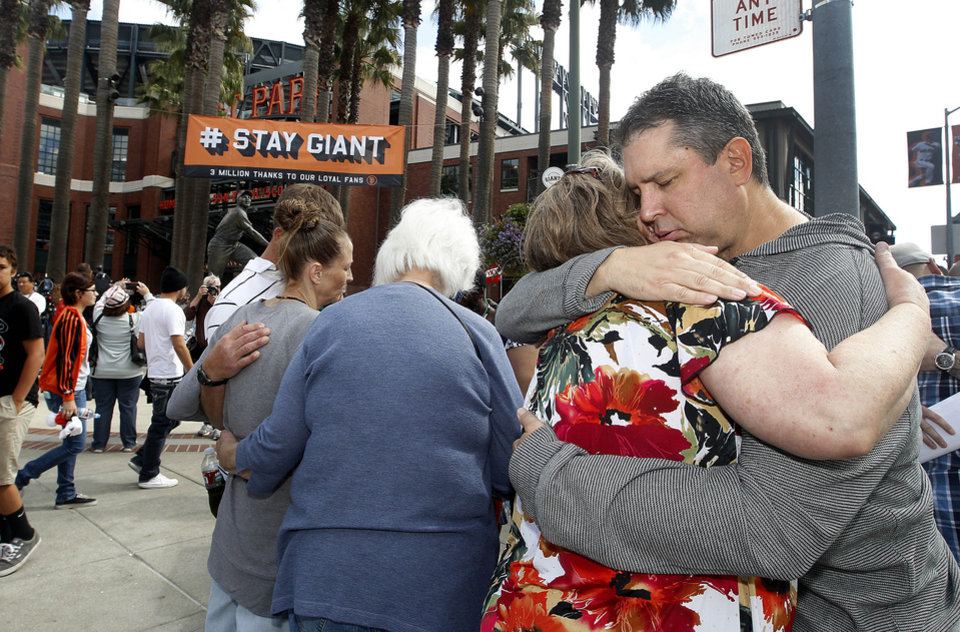 Photo - Robert Preece, right, father of fatally stabbed Los Angeles Dodgers fan Jonathan Denver, hugs family friends before a news conference outside AT&T Park before the Giants' baseball game against the San Diego Padres in San Francisco, Sunday, Sept. 29, 2013. Jonathan Denver, 24, was fatally stabbed Wednesday during a melee following the Giants' game against the Los Angeles Dodgers. (AP Photo/Tony Avelar)