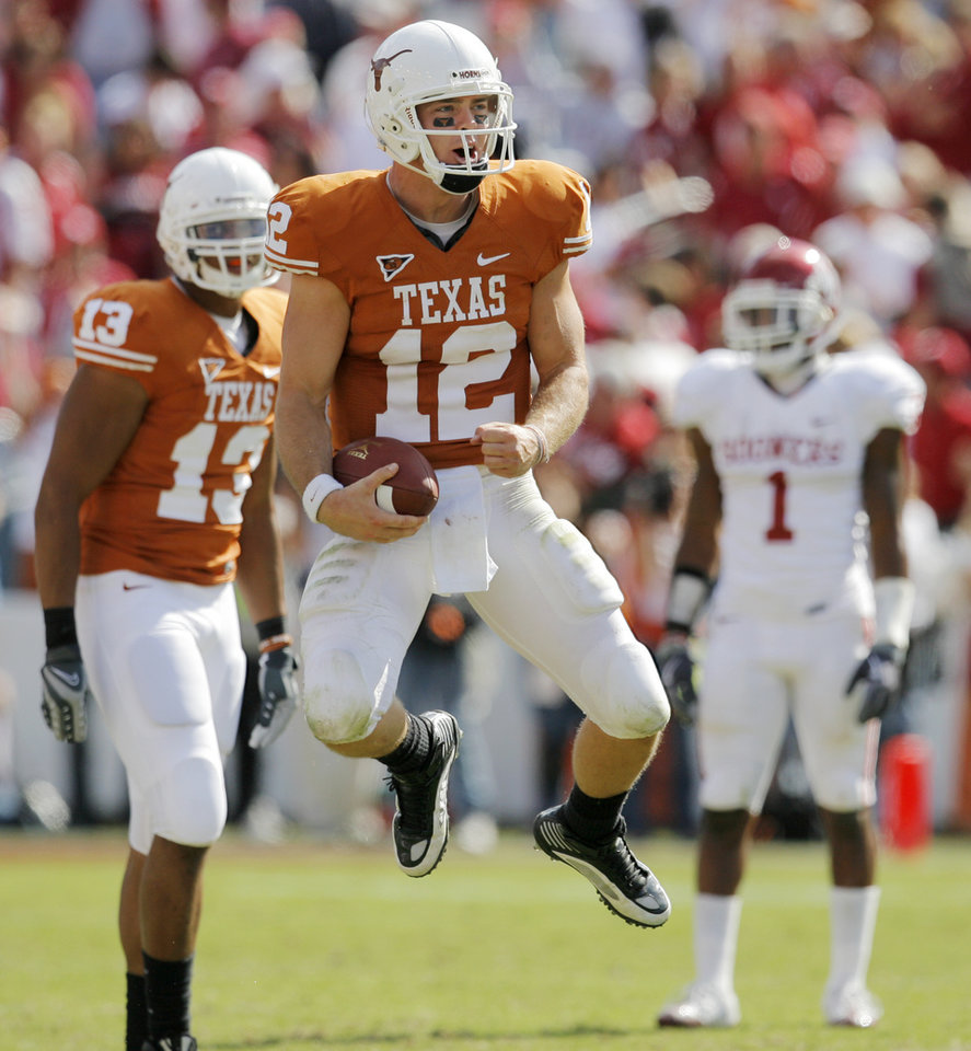 Photo - Texas quarterback Colt McCoy (12) celebrates in front of teammate Ahmard Howard (13) and OU's Dominique Franks (1) after the Red River Rivalry college football game between the University of Oklahoma Sooners (OU) and the University of Texas Longhorns (UT) at the Cotton Bowl in Dallas, Texas, Saturday, Oct. 17, 2009. Texas won, 16-13. Photo by Nate Billings, The Oklahoman