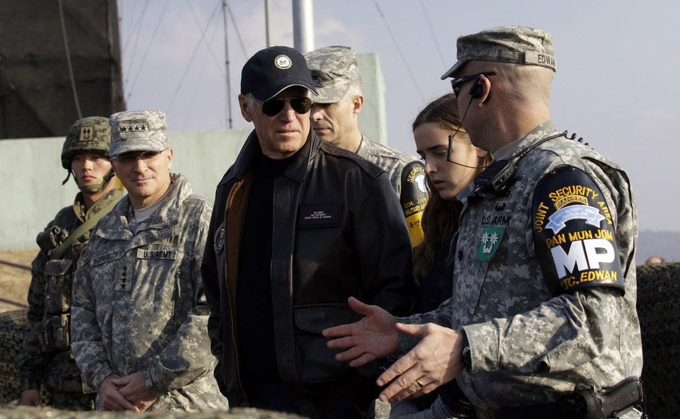 U.S. Vice President Joe Biden, center, is briefed by Lt. Col. Daniel Edwan, the commander of the JSA Security Battalion from Observation Post Ouellette during his tour of the Demilitarized Zone (DMZ), near the border village of Panmunjom, which has separated the two Koreas since the Korean War, South Korea, Saturday, Dec. 7, 2013. (AP Photo/Lee Jin-man, Pool)