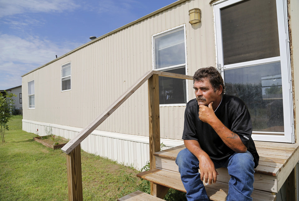 Photo -  Clayton Cook sits on the porch of his mobile home in Steelman Estates. Cook says his younger brother lost $5,000, including FEMA money, in a scam perpetrated by a woman who ostensibly came to 'help' people in the community near Shawnee after an EF-4 tornado struck Pottawatomie County on May 19, 2013. One person died when a tornado destroyed the trailer park. Photos by Jim Beckel, The Oklahoman   Jim Beckel -  THE OKLAHOMAN