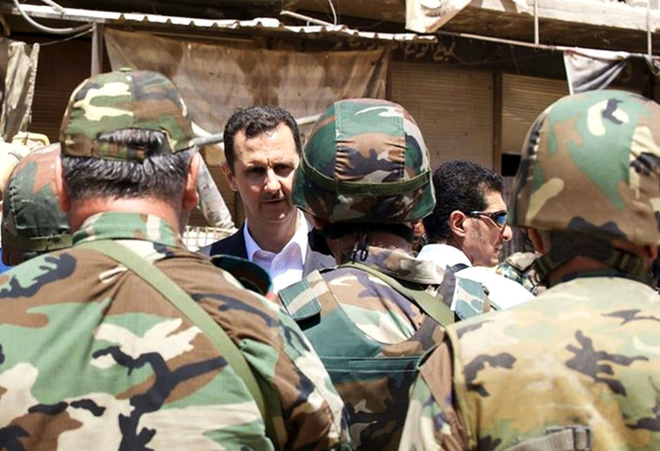 Photo - FILE - This Thursday, Aug.1, 2013 file photo posted on the official Facebook page of the Syrian Presidency, purports to show Syrian President Bashar Assad talking with soldiers with during Syrian Arab Army day in Darya, Syria. As the Obama administration tries to prod Congress into backing armed action against Syria, the regime in Damascus is hiding military hardware and shifting troops out of bases into civilian areas. (AP Photo/Syrian Presidency via Facebook, File)