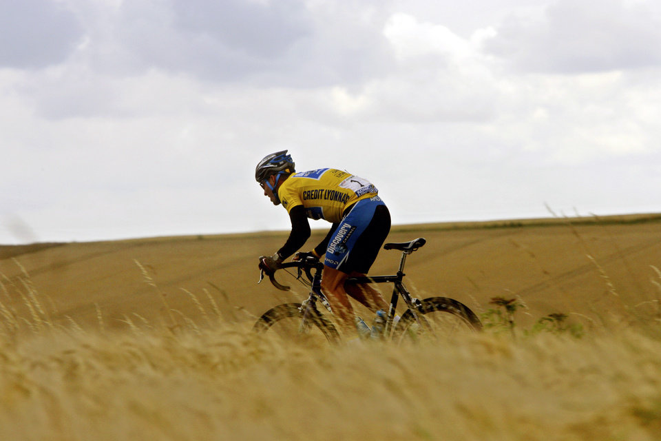 Photo - FILE - In this July 7, 2005, file photo, Lance Armstrong rides through the countryside during the sixth stage of the Tour de France cycling race between Troyes and Nancy, eastern France. In 2005, Armstrong was also named Associated Press Male Athlete of the Year and ESPN's ESPY Award for Best Male Athlete. He later announced what would be a temporary retirement from cycling in 2005. (AP Photo/Alessandro Trovati, File)