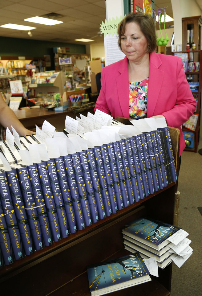 Photo -  Store owner Nan Hight arranges copies of Harper Lee's new book,