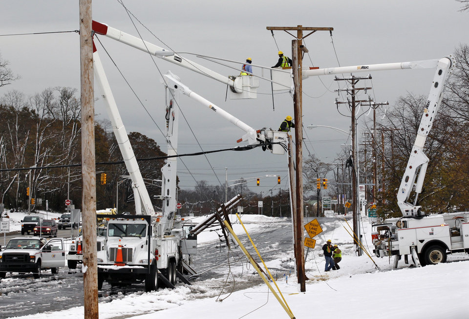 Photo - Crews work to repair downed wires Thursday, Nov. 8, 2012, in Eatontown, N.J., after a nor'easter brought high winds and dumped as much as a foot of snow overnight in the region pounded by Superstorm Sandy last week.  The New York-New Jersey region woke up to a layer of wet snow and more power outages after a new storm pushed back efforts to recover from Superstorm Sandy. (AP Photo/Mel Evans) ORG XMIT: NJME104