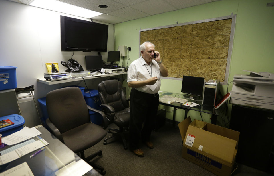 Photo - In this June 25, 2014, photo, Bob Leeds, owner of Sea of Green Farms, a recreational pot grower and processor in Seattle, talks on the phone in his office. Leeds' operation is the first licensed grower in Seattle for recreational marijuana. (AP Photo/Ted S. Warren)