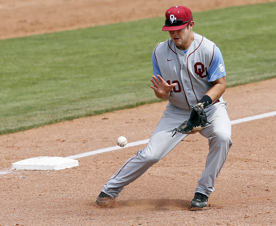 Photo - OU's Garrett Carey (10) fields a ground ball in the 8th inning during an NCAA baseball game between Oklahoma and Texas Tech in the Big 12 Baseball Championship tournament at the Chickasaw Bricktown Ballpark in Oklahoma City, Friday, May 24, 2013. OU won 8-0. Photo by Nate Billings, The Oklahoman