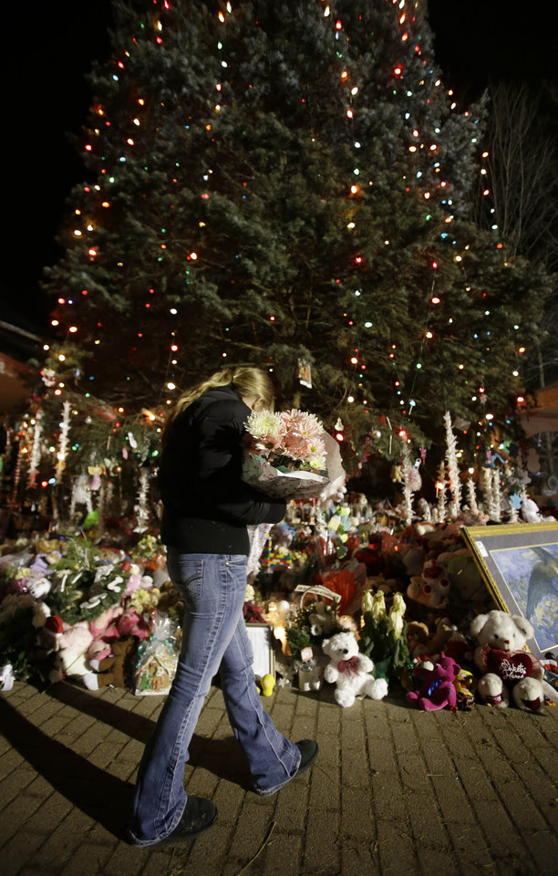 Photo - A woman with flowers walks past a Christmas tree which has become a memorial to the Newtown shooting victims in Newtown, Conn., Thursday, Dec. 20, 2012. (AP Photo/Seth Wenig)