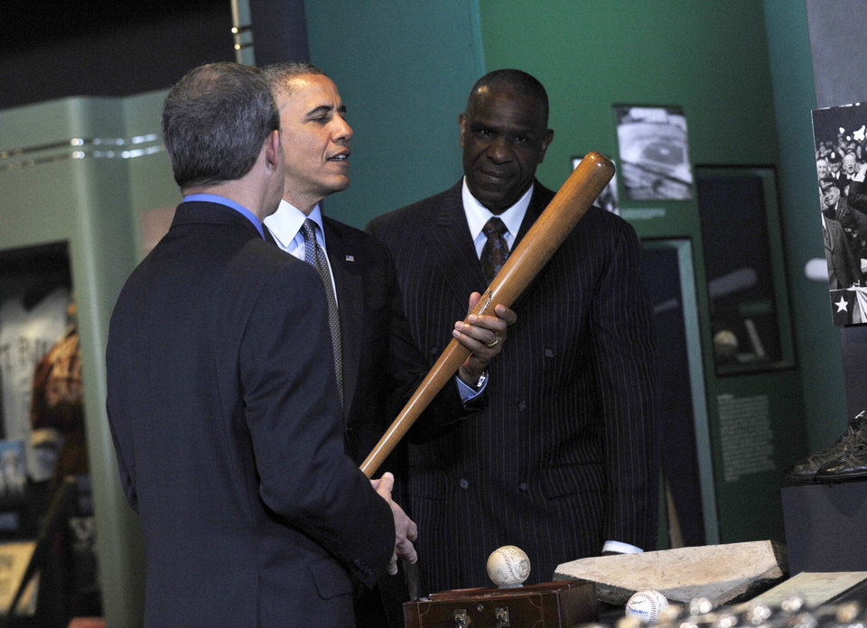Photo - President Barack Obama, accompanied by Baseball Hall of Fame President Jeff Idelson,left, and hall of fame member Andre Dawson, inducted in 2010, holds up Babe Ruth's bat during a tour the Baseball Hall of Fame in Cooperstown, N.Y., Thursday, May 22, 2014. Obama visited the museum to highlight tourism and steps to help spur international visits to the 50 states. Obama said the overall U.S. economy and local businesses will benefit if it isn't a hassle for people from other countries to visit the U.S. and spend money at its hotels, restaurants, tourist destinations and other businesses. (AP Photo/Susan Walsh)