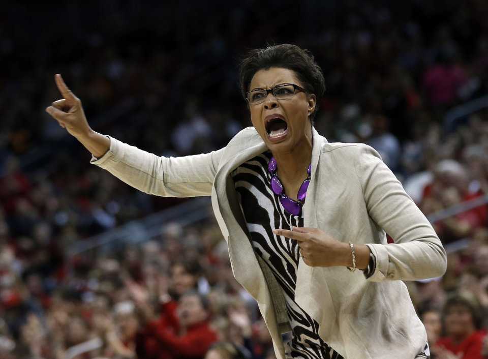 Photo - LSU head coach Nikki Caldwell directs her players from the bench during the first half of a regional semifinal game against Louisville at the NCAA college basketball tournament on Sunday, March 30, 2014, in Louisville, Ky. (AP Photo/John Bazemore)
