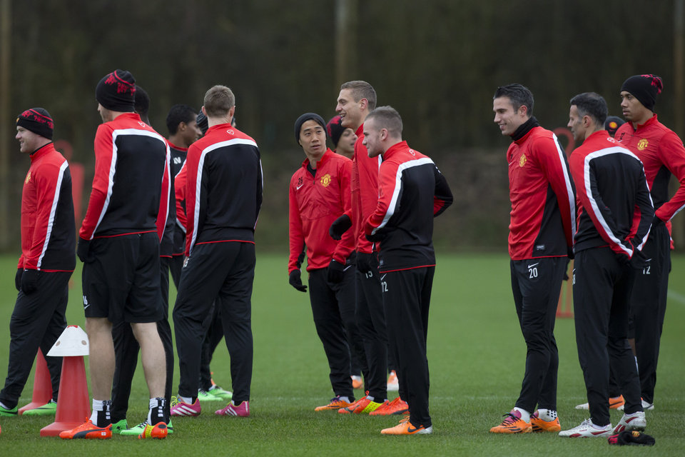Photo - Manchester United's Shinji Kagawa, centre, looks on as teammate Nemanja Vidic, centre right, laughs during training session at Carrington training ground in Manchester, Monday, Feb.24, 2014. Manchester United will play Olympiakos in a Champions League first knockout round on Tuesday. (AP Photo/Jon Super)