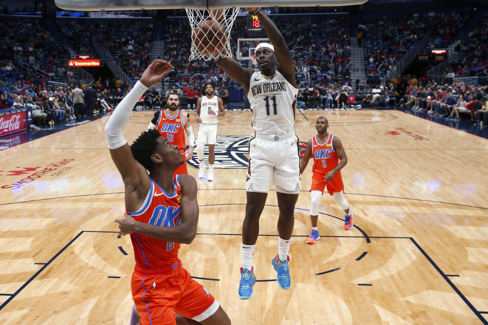 Photo - New Orleans Pelicans guard Jrue Holiday (11) slam-dunks over Oklahoma City Thunder guard Shai Gilgeous-Alexander (2) in the first half of an NBA basketball game in New Orleans, Sunday, Dec. 1, 2019. (AP Photo/Gerald Herbert)