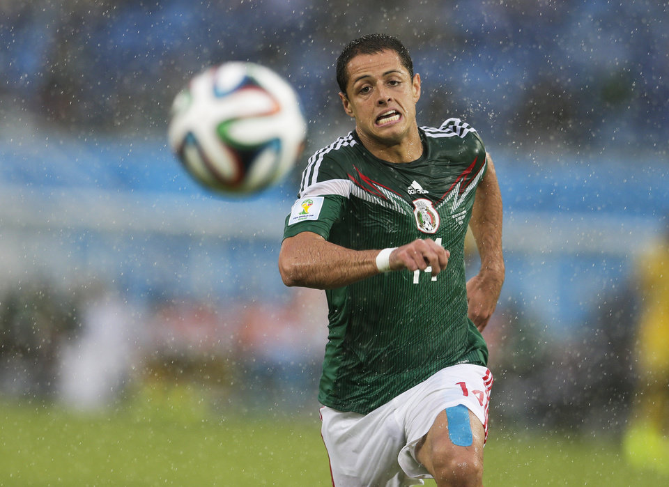 Photo - Mexico's Javier Hernandez chases the ball in downpour during the group A World Cup soccer match between Mexico and Cameroon in the Arena das Dunas in Natal, Brazil, Friday, June 13, 2014. Mexico defeated Cameroon 1-0. (AP Photo/Petr David Josek)