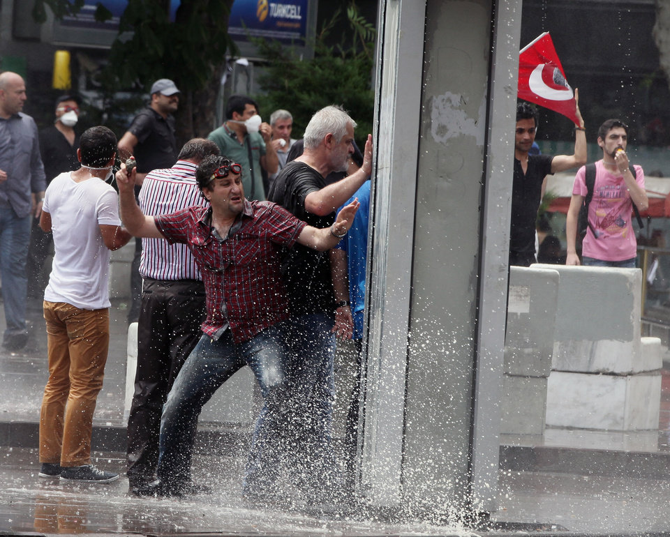 Photo - A protester throws a stone toward police as Turkish riot police spray water cannon at demonstrators who remained defiant after authorities evicted activists from an Istanbul park, making clear they are taking a hardline against attempts to rekindle protests that have shaken the country, in city's main Kizilay Square in Ankara, Turkey, Sunday, June 16, 2013.(AP Photo/Burhan Ozbilici)