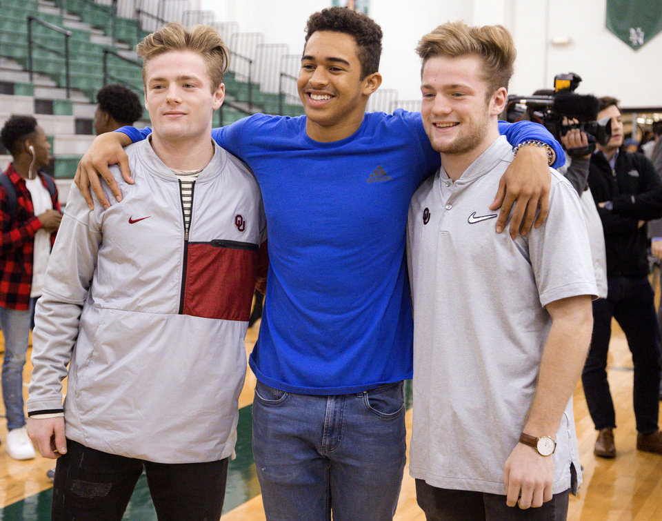 Photo - Norman North's Ryan Peoples, center,  poses for a photo with Drake and Issac Stoops, from left, after signing his letter of intent to play football for Northeastern Oklahoma University during national signing day at Norman North High School in Norman, Okla. on Wednesday, Feb. 7, 2018. The Stoops brothers will be preferred walk-ons to play football for the University of Oklahoma.  Photo by Chris Landsberger, The Oklahoman