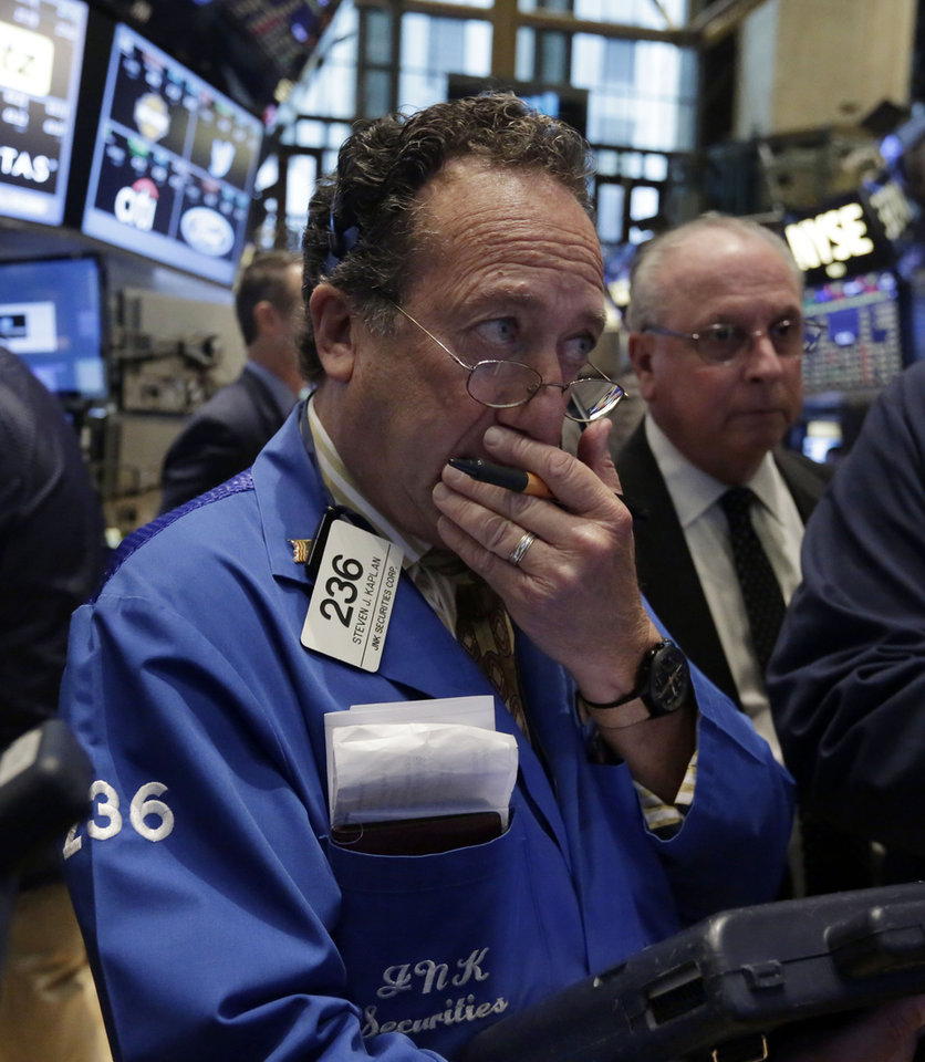 Photo - Trader Steven Kaplan, left, works on the floor of the New York Stock Exchange Wednesday, Aug. 6, 2014. Worries about Russian troops massing near the Ukrainian border are pushing stocks slightly lower. U.S. stocks are little changed in early trading Wednesday as investors worry about escalating tensions between Russia and the Ukraine. Investors were also holding back after two larger merger bids were pulled. (AP Photo/Richard Drew)