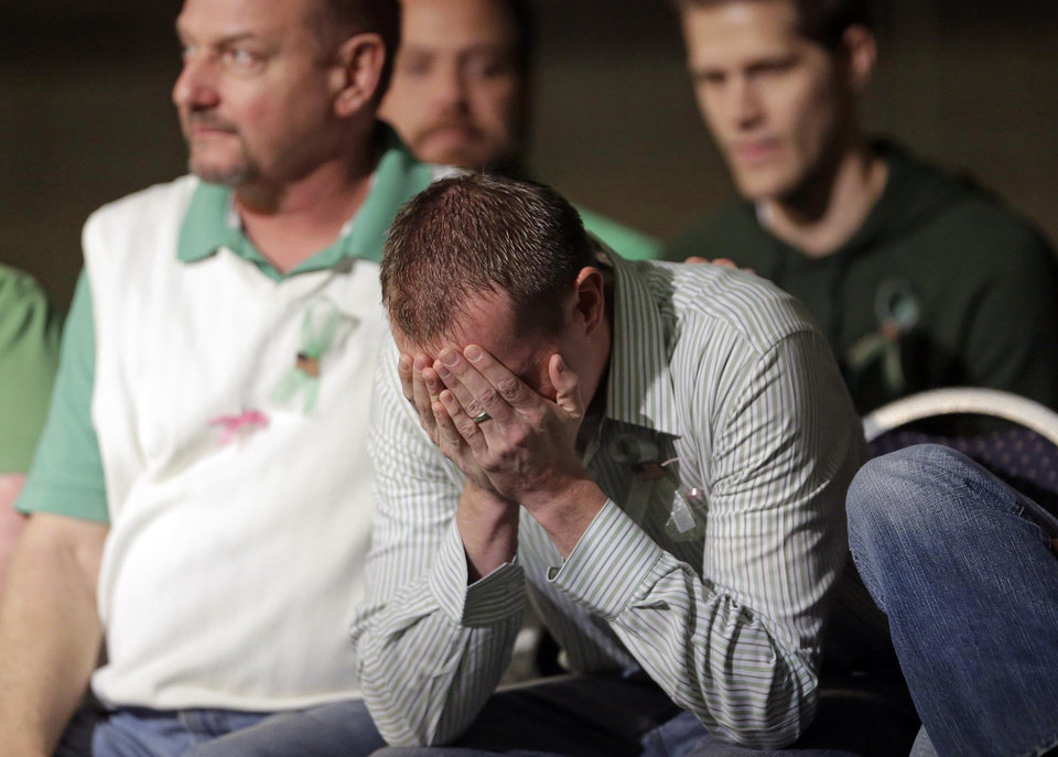 Robbie Parker, the father of a 6-year-old Emilie Parker, killed in last week's Connecticut school shooting, lowers his head after making remarks to family and friends during a memorial service Thursday, Dec. 20, 2012, at the Ben Lomond High School, in Ogden, Utah. (AP Photo/Rick Bowmer)