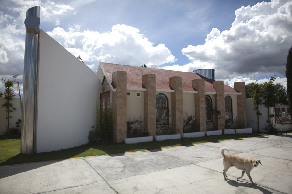Photo -   A dog walks near a tomb that was allegedly built by Heriberto Lazcano Lazcano, alleged leader of the Zetas, at a cemetery in the neighborhood of Tezontle in Pachuca, Mexico, Tuesday, Oct. 9, 2012. The tomb is a copy of an actual church in Tezontle, which at one point had a plaque naming Lazcano as the donor. Mexico's Navy says fingerprints confirm that cartel leader Lazcano, an army special forces deserter, was killed Sunday, Oct. 7, 2012 in a firefight with marines in the northern state of Coahuila on the border with the Texas. (AP Photo/Alexandre Meneghini)