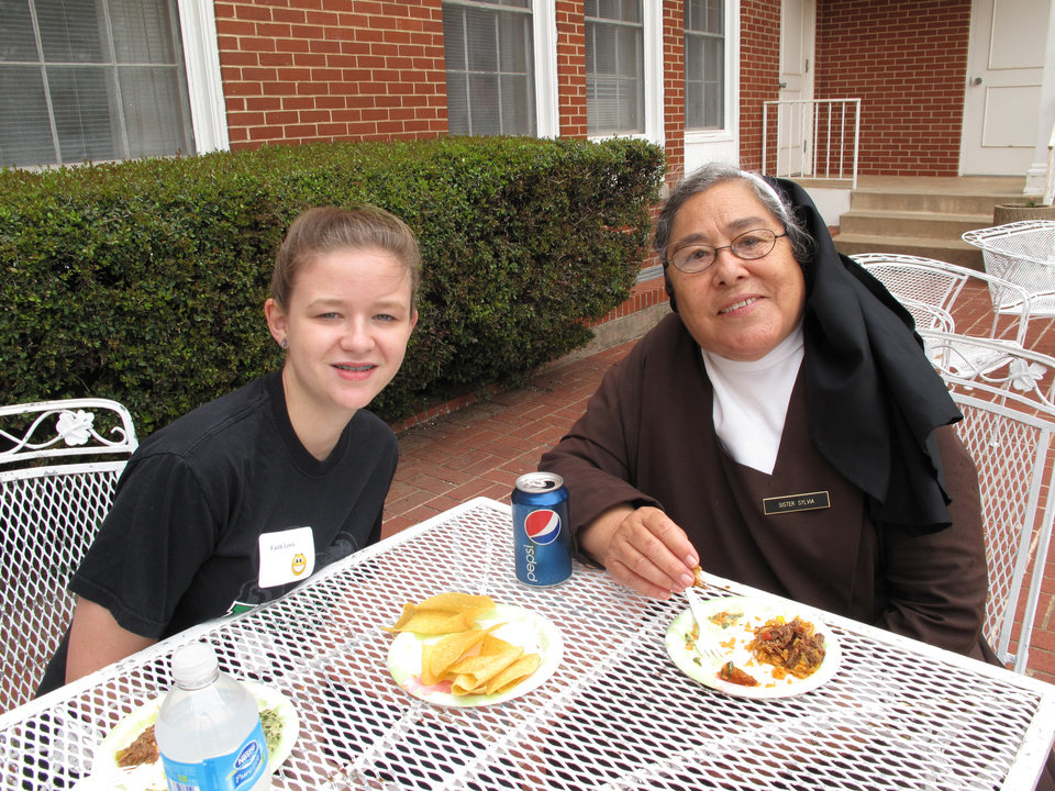 Photo - Faith Lewis, 14, and Sister  Sylvia Negrete eat together during the recent Carmelite Sisters of St. Therese alumni event at Villa Teresa Convent and School in Oklahoma City. Photo by Carla Hinton  Carla Hinton - The Oklahoman