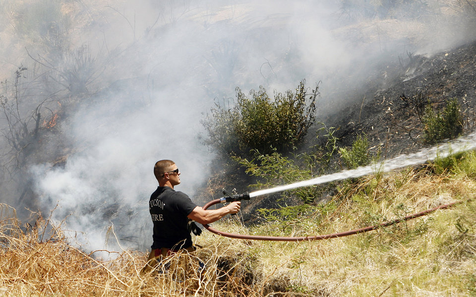 Tucson firefighter Lyle Steffens, sprays water on a brush fire Thursday in midtown Tucson, Ariz  Photo by Benjie Sanders, Arizona Daily Star/AP photo