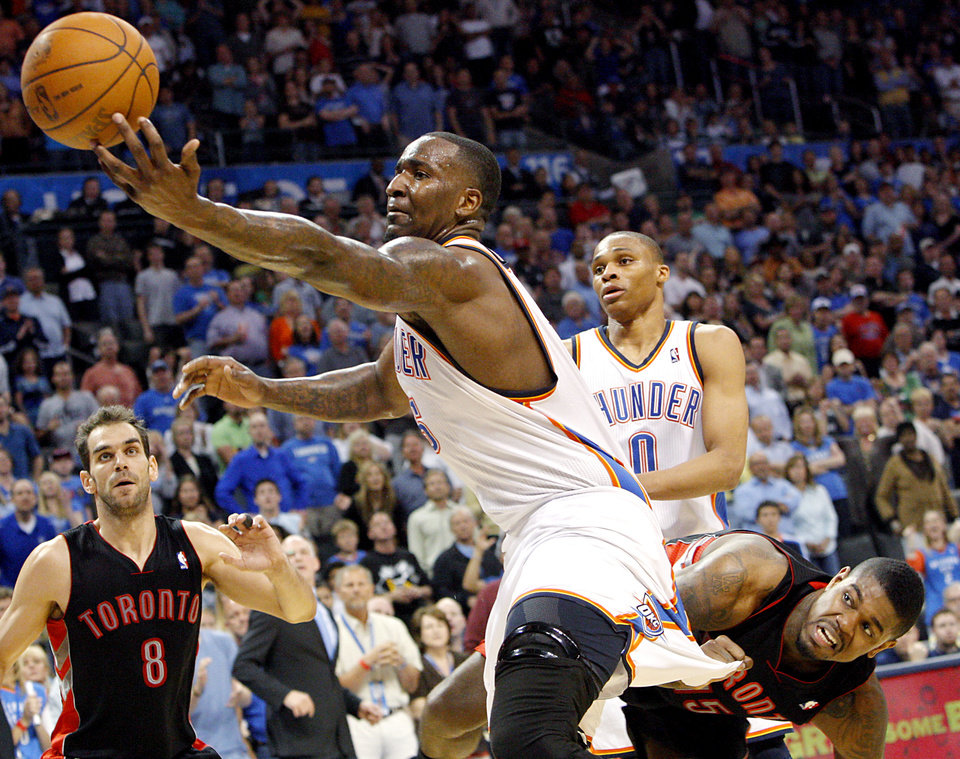 Photo - Oklahoma City's Kendrick Perkins is pulled away from a rebound by Toronto's Amir Johnson during the second half of their NBA basketball game at the OKC Arena in downtown Oklahoma City on Sunday, March 20, 2011. The Raptors beat the Thunder 95-93. Photo by John Clanton, The Oklahoman