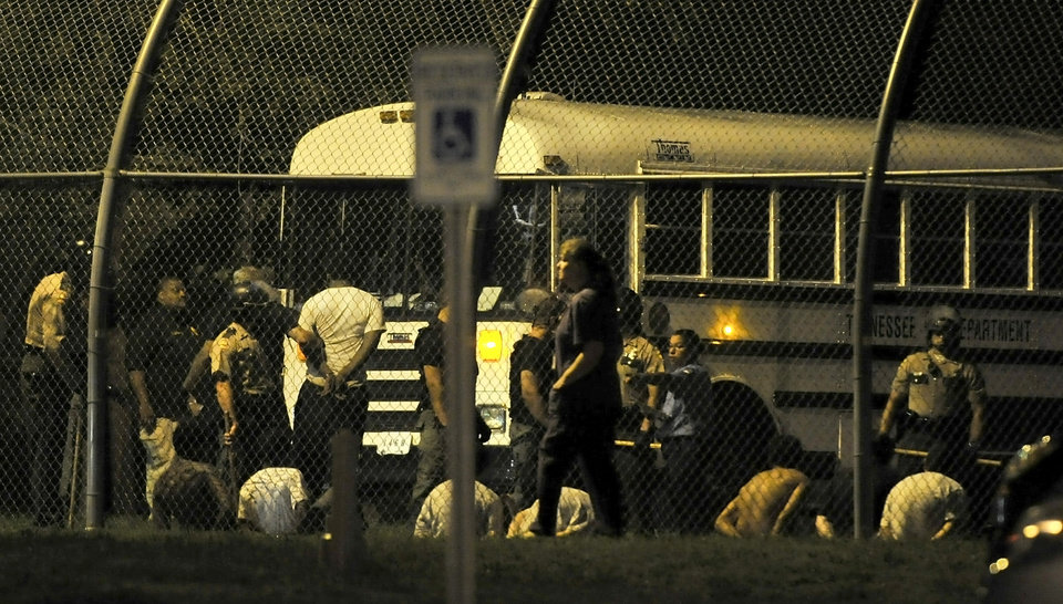 Photo - Teenagers are escorted to an awaiting Tennessee Department of Correction bus in custody after a riot at Woodland Hills Youth Development Center in Nashville, Tenn., early Thursday, Sept. 4, 2014. More than two dozen teens created a large disturbance Wednesday night in the yard of a detention center with a long history of violence, escape attempts and sexual-abuse allegations. 32 teens escaped from the facility two days earlier. (AP Photo/The Tennessean, Jae S. Lee)