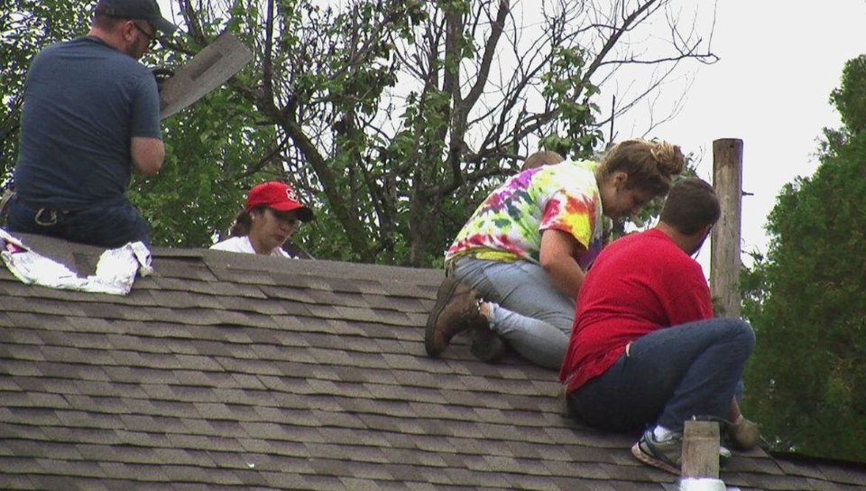 Photo -  Volunteers with the Bounce Student Disaster Recovery program work to repair the roof of an Oklahoma City child care center. Photo by Grayson Cook, The Oklahoman