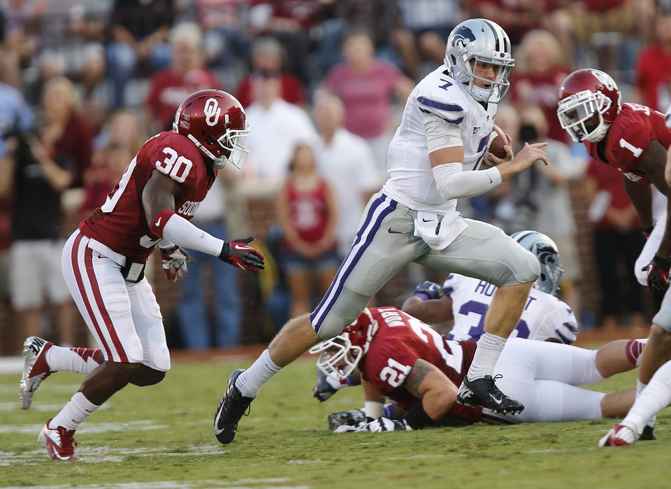 Photo - Kansas State's Collin Klein(7) runs past Oklahoma's Javon Harris (30) during the college football game between the University of Oklahoma Sooners (OU) and the Kansas State University Wildcats (KSU) at the Gaylord Family-Memorial Stadium on Saturday, Sept. 22, 2012, in Norman, Okla. Photo by Chris Landsberger, The Oklahoman
