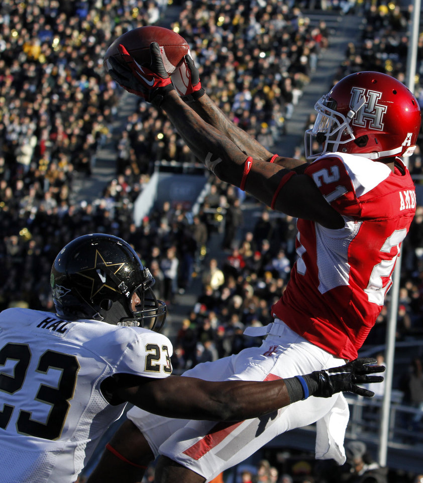 Photo - Houston wide receiver Markeith Ambles  (21) catches a pass over Vanderbilt defensive back Andre Hal (23) for a touchdown during the second half of the BBVA Compass Bowl NCAA college football game on Saturday, Jan. 4, 2014, in Birmingham, Ala. Vanderbilt defeated Houston 41-24. (AP Photo/Butch Dill)