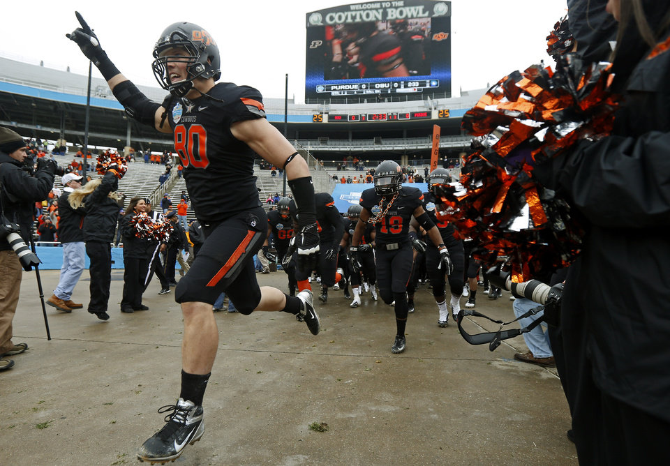 Photo - The Oklahoma State football team takes the field before the Heart of Dallas Bowl football game between Oklahoma State University and Purdue University at the Cotton Bowl in Dallas, Tuesday, Jan. 1, 2013. Oklahoma State won 58-14. Photo by Bryan Terry, The Oklahoman