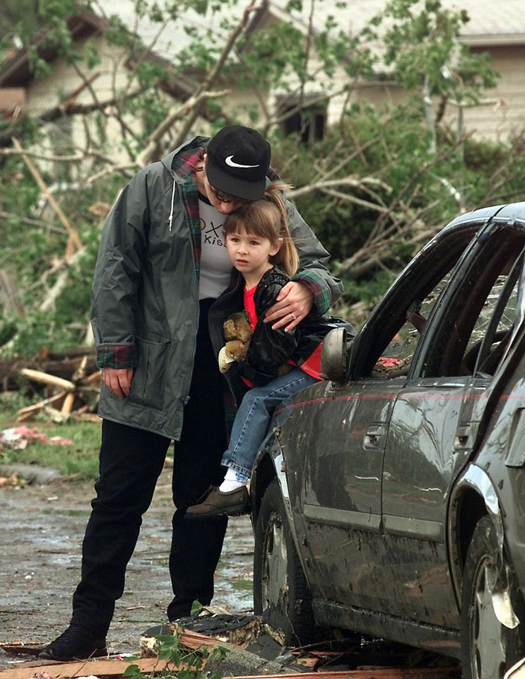 MAY 3, 1999 TORNADO: Tornado victims: Christy Thomas hugs her 4-year-old daughter, Danielle on the hood of a car on the street in front of their home at 6101 SE 7th in MWC. They were not at home when the tornado hit Monday night.