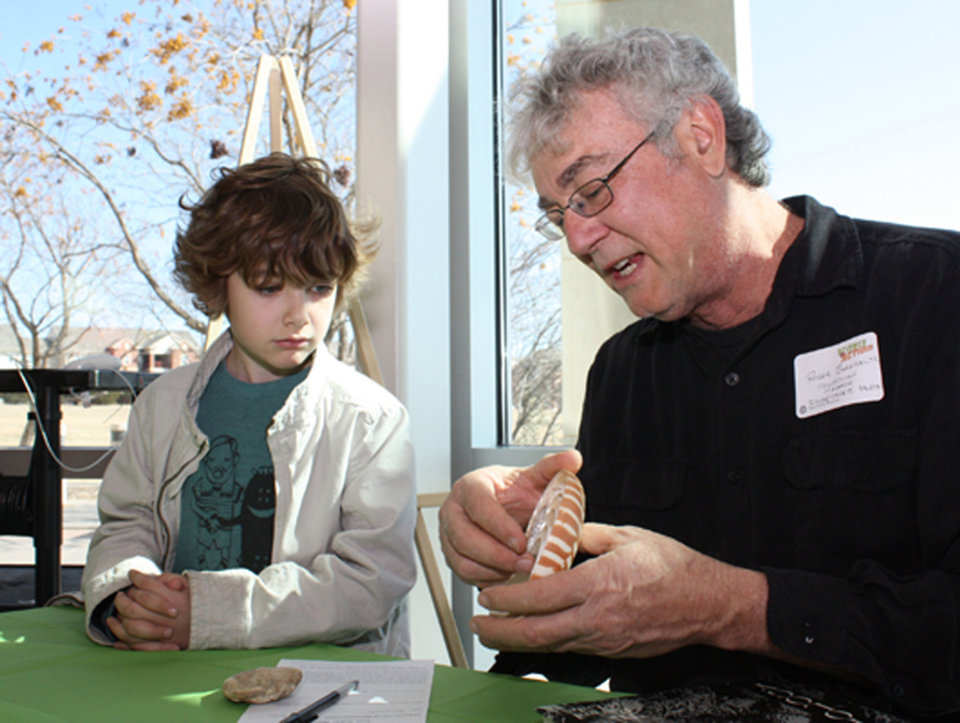 Aidann Attaway, 8, and scientist Roger Burkhalter discuss the ammonite and oyster Aidann brought Sunday to the Sam Noble Oklahoma Museum of Natural History's annual Object Identification Day.  PHOTOs BY LYNETTE LOBBAN, FOR THE OKLAHOMAN