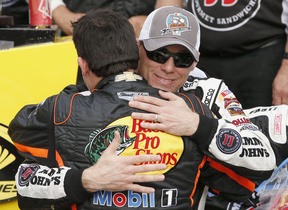 Photo - Kevin Harvick, right, gets a hug from Tony Stewart after Harvick woin the NASCAR Sprint Cup Series auto race Sunday, March 2, 2014, in Avondale, Ariz. (AP Photo/Ross D. Franklin)