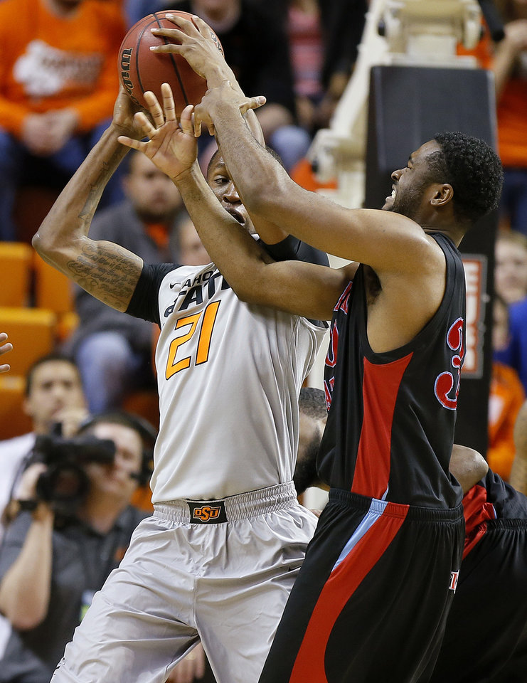 Photo - Oklahoma State's Kamari Murphy (21) tries to pass around Delaware State's Jordan Lawson (30) during an NCAA college basketball between Oklahoma State University and Delaware State at Gallagher-Iba Arena in Stillwater, Okla., Tuesday, December 17, 2013. Photo by Bryan Terry, The Oklahoman