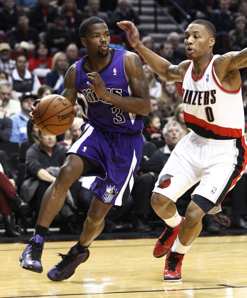 Sacramento Kings guard Aaron Brooks, left, drives the baseline against Portland Trail Blazers guard Damian Lillard during the first quarter of their NBA basketball game in Portland, Ore., Saturday, Dec. 8, 2012.(AP Photo/Don Ryan)