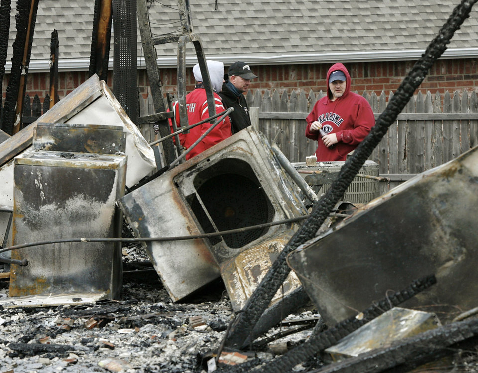 Photo - David Dolney, far right, and relatives look at damage to the home where he and his wife, Niki, lived in Oakwood East Royale neighborhood, 11365 Queensland Ct.  The house was one of numerous structures destroyed in Thursday's wildfires. Photo by Jim Beckel, The Oklahoman