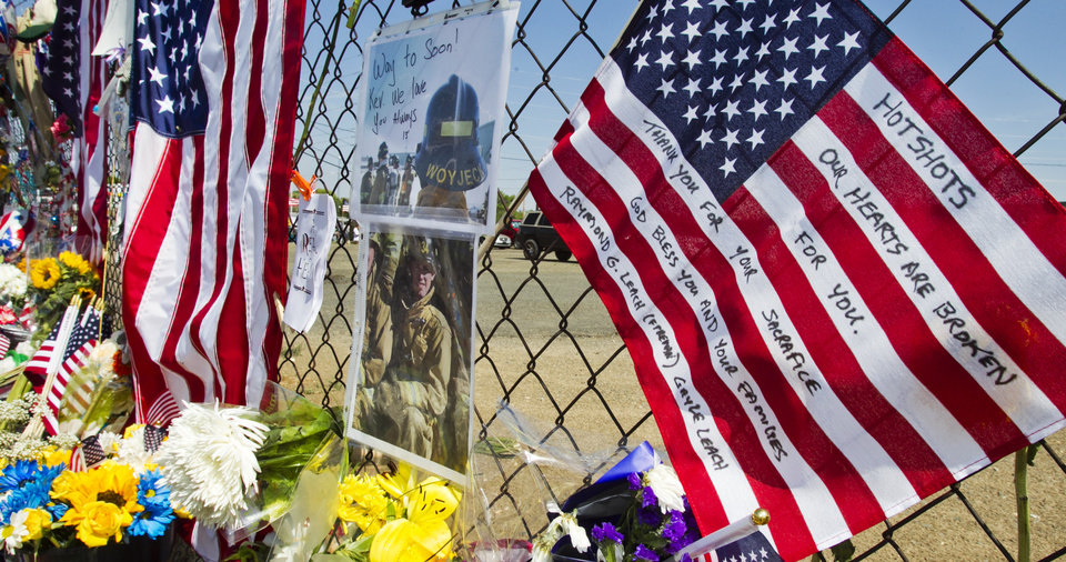Photo - Mementos are posted on a fence outside Fire Station 7 in Prescott, Ariz. on Tuesday, July 2, 2013 in a makeshift memorial for the 19 Granite Mountain Hotshots who were killed by an out-of-control blaze near Yarnell, Ariz. on Sunday. (AP Photo/The Arizona Republic, Tom Tingle)