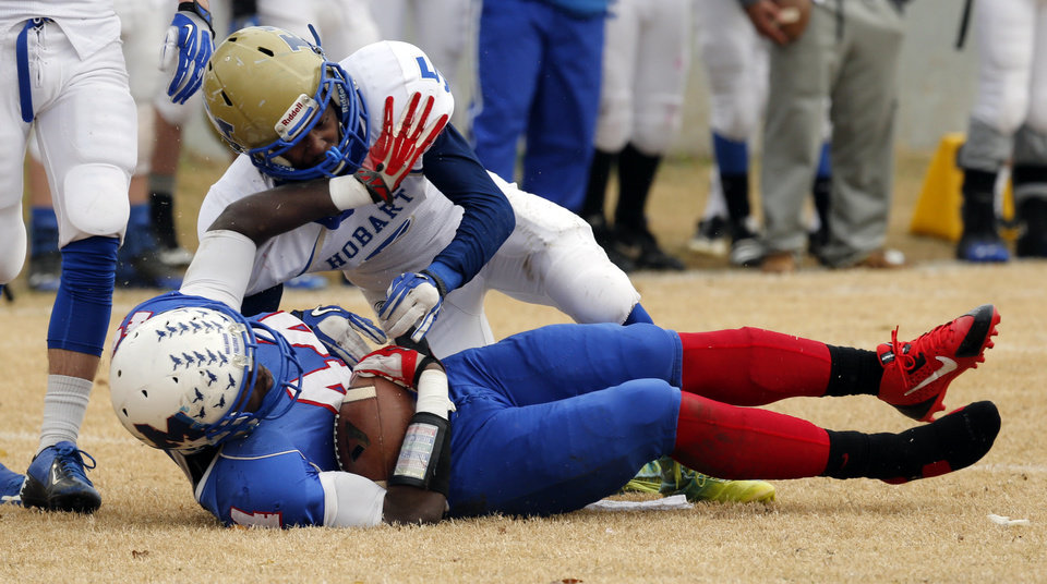 Photo - Hobart's Shawn Clark brings down Millwood's Larry Lambeth after a catch in high school football playoff action on Saturday, Nov. 23, 2013, in Oklahoma City, Okla. Photo by Steve Sisney, The Oklahoman