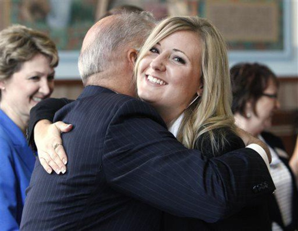 Photo - Bridgette Brown, of Oklahoma City, gets a hug from Oklahoma County District Attorney David Prater as she receives her diploma during the ReMerge graduation ceremonies at the Oklahoma County Courthouse in Oklahoma City on Tuesday. The ReMerge program is an alternative to prison for mothers and pregnant women who are facing charges for nonviolent crimes. The Oklahoman, Paul B. Southerland  PAUL B. SOUTHERLAND