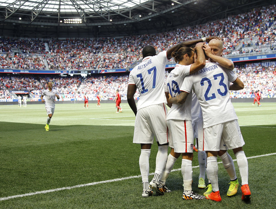 Photo - United States' Fabian Johnson (23) is congratulated by teammates after scoring a goal against Turkey in the first half of an international friendly soccer match on Sunday, June 1, 2014, in Harrison, N.J. (AP Photo/Julio Cortez)