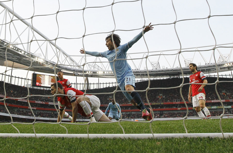 Photo - Manchester City's David Silva celebrates scoring a goal during the English Premier League soccer match between Arsenal and Manchester City at the Emirates stadium in London, Saturday, March 29, 2014. (AP Photo/Kirsty Wigglesworth)